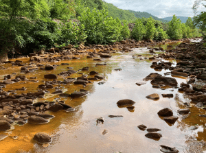 Pictured is the lower portion of Deckers Creek looking upstream to the former Richard Mine, which has left behind a legacy of degraded water quality throughout the creek. But a new planned acid mine drainage treatment system promises to clean up this stretch of the creek in Monongalia County.